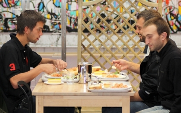 Three persons having lunch at the social restaurant of the Foundation in Metz