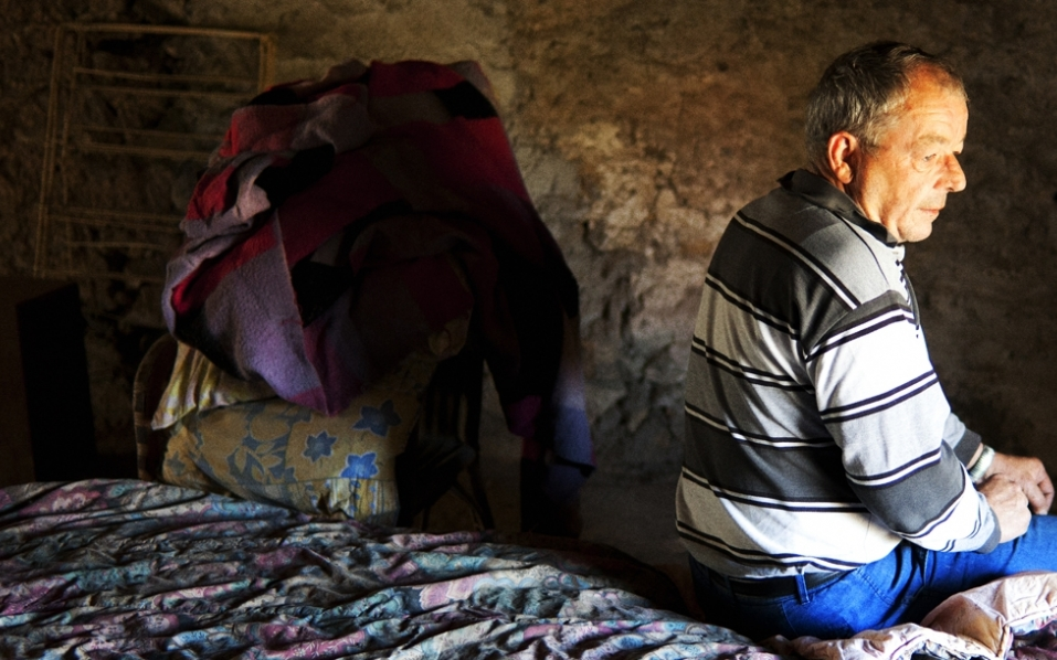 A man living in a slum, sitting on his bed